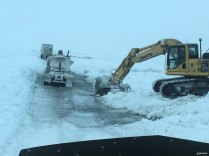 The excavator is moving snow and slush away from the road to keep the water flowing to where they want it to go.
