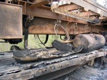 This diesel tank probably burned because there was fuel in it. It didn't explode. At some point the metal straps that were holding the tanks up to the truck melted and the tanks dropped onto the trailer. The burnt piece of wood most likely came from the wood deck of the flat bed.