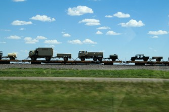 Military vehicles being hauled on rail.