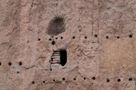 Post holes for supporting the rock buildings that leaned against the cliff wall. (The engraving may be vandalism.)